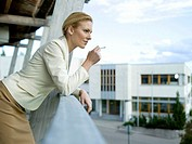 Businesswoman smoking on balcony
