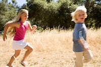 Young girl and young boy running in park