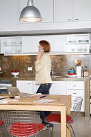 Businesswoman walking through kitchen area