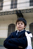 Young boy wearing a suit in courtyard