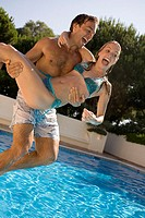 Young couple jumping in pool