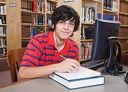 Teenage boy writing in notebook in library