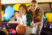 Boy and woman bowling