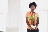 Mid-adult woman holding plant in office