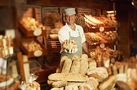 Man holding loaf of bread in bakery