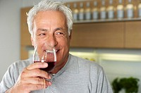 Gray-haired man with a glass of wine in his hand, close-up