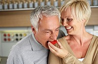 Gray-haired man biting in a slice of a tomato which a woman is holding, close-up