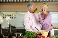 Blond woman feeding a man with a lettuce leaf