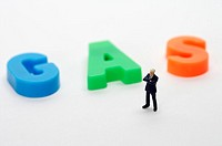 Businessman figurine standing next to the word gas