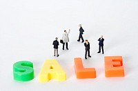 Businessmen figurine standing next to the word sale