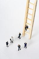 Businessmen figurines standing next to a ladder, one figurine sitting on a rung