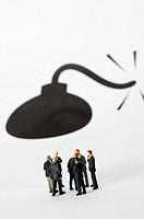 Group of businessmen figurines standing in circle, picture of a bomb in background