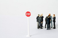 Group of businessmen figurines standing in circle, stop sign in foreground