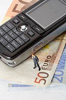 Businessman figurine next to mobile phone on a stack of Euro banknotes