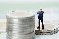 Businessman figurine standing on a stack of coins