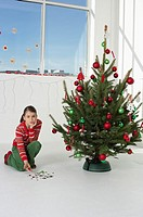 Girl picking up Christmas tree ball shards