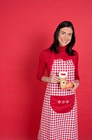 Woman wearing a chequered apron holding a gingerbread
