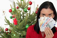Woman holding banknotes, Christmas tree in background
