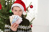 Boy wearing Santa hat holding banknotes