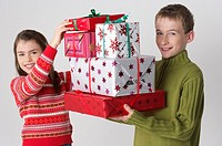 Girl and boy with a stack of Christmas presents