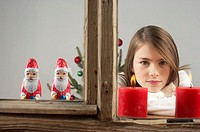 Girl looking out of a window with candles and Santa Claus chocolates