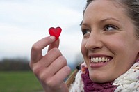 Young woman with scarf is holding a gummi-bear heart in her hand , close-up