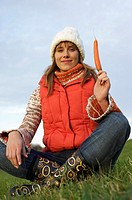 Yong woman in warm clothing sitting on a meadow while holding a carrot in her hand