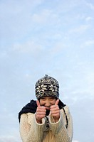 Young woman with scarf and cardigan under the sky holding her thumbs up, close-up