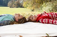 Two young women lying head to head on a sheet in a park, selective focus
