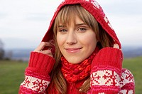 Young woman with scarf and cardigan putting on a hood, close-up