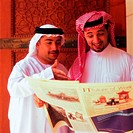 Arab men reading newspaper