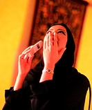 Arab woman laughing while using a cell phone