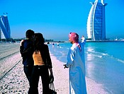 Arab man shows western tourists the Burj Al Arab hotel in Dubai, UAE