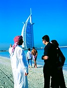Arab man shows Burj Al Arab hotel to western couple, Dubai, UAE (thumbnail)