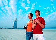 Western tourists on the beach near Burj Al Arab hotel in Dubai, UAE