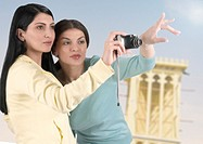 Two Arab women taking pictures of Dubai landmarks