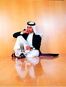 Saudi Arabian businessman sitting on office floor (thumbnail)