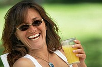 Close-up of a young woman holding a glass of orange juice and laughing