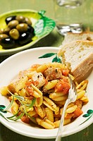 Pasta with meat and tomato sauce, white bread, olives