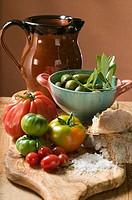 Fresh tomatoes, olives, bread, salt and terracotta jug