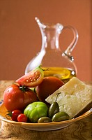 Tomatoes, green olives and Parmesan on plate, olive oil