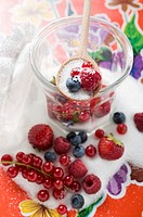 Fresh berries in jam jar with sugar and wooden spoon