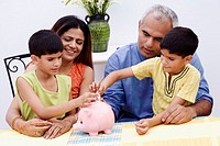 Two boys inserting Indian currency notes into a piggy bank with their parents sitting beside them