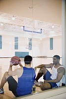 Two men sitting on basketball court
