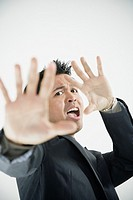 Scared Asian businessman with hands up