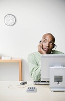 African businessman leaning chin on hand at desk