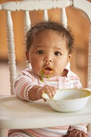 African baby in highchair with food on face