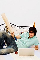 Portrait of a young man holding a cricket bat in front of a laptop on the bed
