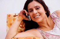 Portrait of a mid adult woman lying on a couch and talking on a mobile phone