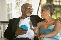 Senior African couple in formal dress with gift and cocktail